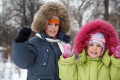 Brother and sister smiling in winter forest Royalty Free Stock Images