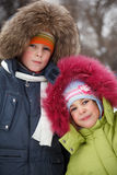 Brother and sister smiling in winter forest Stock Photo