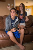 Brother and Sister - Sneak attack. Tween sister (girl) about to cover her brother (boys) eyes while he is playing a video game.  Both kids are on a couch in the Royalty Free Stock Photography