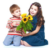 Brother and sister sniffing bouquet of sunflowers stock photography
