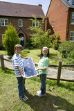 Brother and sister (6-10) with solar panel by house, portrait Royalty Free Stock Photos