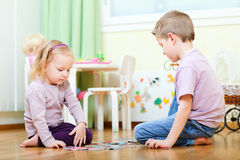 Brother and sister solving puzzle Royalty Free Stock Photography
