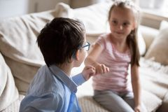 Brother and sister squeeze little fingers as sign of reconciliation. Boy and girl put up after having fight, conflict, quarrel at home. Siblings relationship stock photo