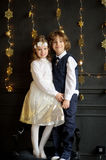 The brother and the sister stand having embraced. The girl is dressed in a white and gold elegant dress. On the head of her a wreath. The boy has a bowtie Royalty Free Stock Photo