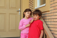 Brother and sister stand near door of cottage. And look into camera Stock Photography