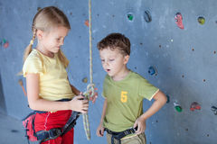 Brother and sister standing near a rock wall for climbing Stock Image