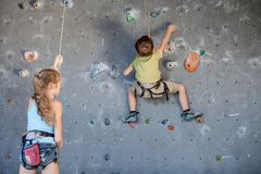 Brother and sister standing near a rock wall for climbing indoor. Concept of sport life stock photo
