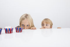 Brother and sister staring at cupcakes on table Stock Photos