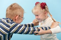 Brother and sister start a fight with each other. Over blue Royalty Free Stock Image