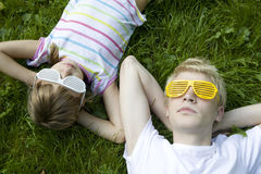 Brother and sister in strange sunglasses lying Royalty Free Stock Photos