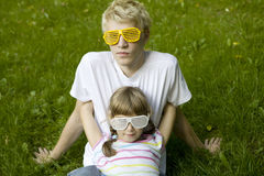 Brother and sister in strange sunglasses sitting Royalty Free Stock Image