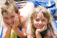 Brother and Sister After Swim. Kids lying on a towel after swimming Royalty Free Stock Images