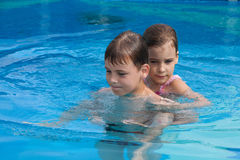 Brother sister swim play in pool Stock Photo