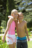 Brother and sister (7-11) in swimsuits arm in arm in garden, smiling, portrait Stock Photos