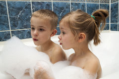 Brother and sister taking a bubble bath. Little boy and girl pla Stock Image