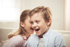 Brother and sister talking and gossiping together while sitting on sofa at home Royalty Free Stock Images