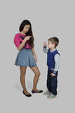 Brother and sister. Teenage girl and little boy point the finger at each other on gray background - dispute, disagreement, accusation, blame concept Royalty Free Stock Photography