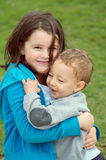 Brother and sister tenderness. Natural portrait of big sister holding tightly and happily toddler brother in a tender moment royalty free stock photography