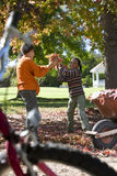 Brother and sister throwing autumn leaves stock photo