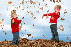 Brother and Sister Throwing Leaves royalty free stock photography