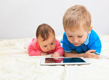 Brother and sister with touch pad Stock Photos