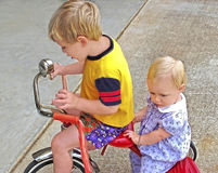 Brother and Sister on a Tricycle. Young boy ready to give his sister a ride on a tricycle, she seems unsure about it stock photos