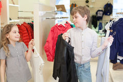 Brother with sister trying on clothes in store. Childrens clothes, focus on the boy royalty free stock photography