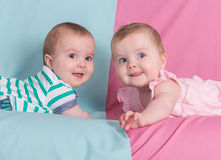 Brother and sister. Twins babies girl and boy on pink and blue background Royalty Free Stock Photo