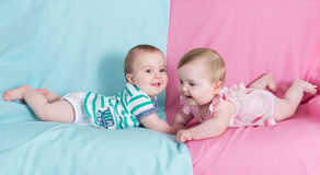 Brother and sister. Twins babies girl and boy on pink and blue background Stock Photos