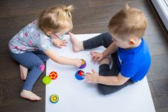 Brother and sister twins learn how to paint. By hands stock image