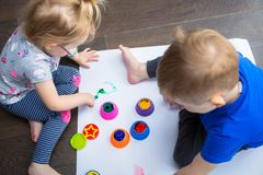 Brother and sister twins learn how to paint. By hands stock photo