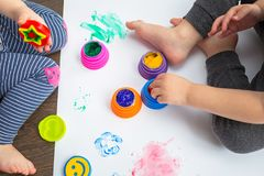 Brother and sister twins learn how to paint. By hands stock images