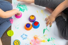 Brother and sister twins learn how to paint. By hands stock photography