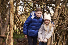 Brother and sister under shelter of branches look to camera Royalty Free Stock Photo