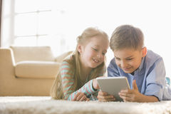 Brother and sister using digital tablet on floor at home Royalty Free Stock Image