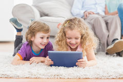 Brother and sister using digital tablet on rug Royalty Free Stock Image