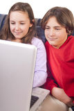 Brother and sister using a laptop computer Stock Images