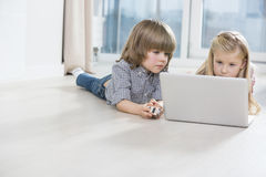 Brother and sister using laptop on floor at home Stock Photos