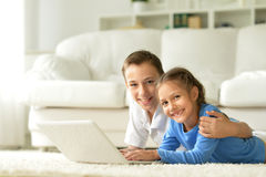 Brother and sister using laptop. Lying on the carpet Royalty Free Stock Photo