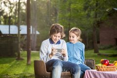 Brother And Sister Using Smartphone At Campsite Stock Photography