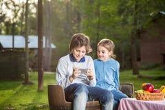 Brother And Sister Using Smartphone en el sitio para acampar Fotografía de archivo