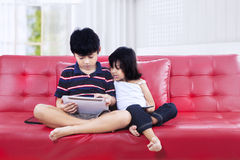 Brother and sister using tablet on the couch Royalty Free Stock Photo