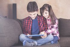 Brother and sister using tablet at home. Kids and technology concept with kids having fun with their tablet Stock Photos