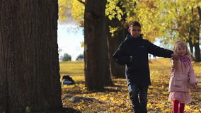 Brother and sister walking in the autumn park. The little boy and a little girl are going holding hands. Yellow leaves are on the road and around. Children are stock footage