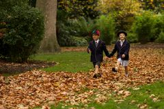 Brother and sister walking hand-in-hand through leaves Royalty Free Stock Images