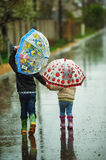 Brother and sister walking in the rain holding umbrellas. Children walk in the rain holding umbrellas Royalty Free Stock Photo