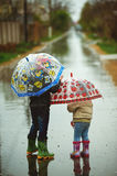 Brother and sister walking in the rain holding umbrellas. Children walk in the rain holding umbrellas Royalty Free Stock Image