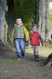 Brother and sister walking in the woods Royalty Free Stock Photos
