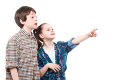 Brother and sister watching something. Let me show you. Small pretty girl standing next to her older brother and pointing somewhere with her finger while her royalty free stock photos
