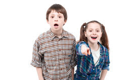 Brother and sister watching something. Look at this. Small pretty girl standing next to her older brother and pointing at you with her finger while her brother stock photos